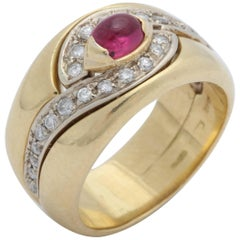 1980s Chic Cabochon Ruby with Diamond Swirl Design Gold Band Style Ring
