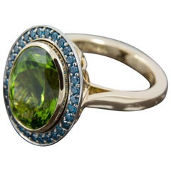 8.35 Carat Peridot and Blue Diamond Halo Cocktail Ring set in 18 Karat Gold
