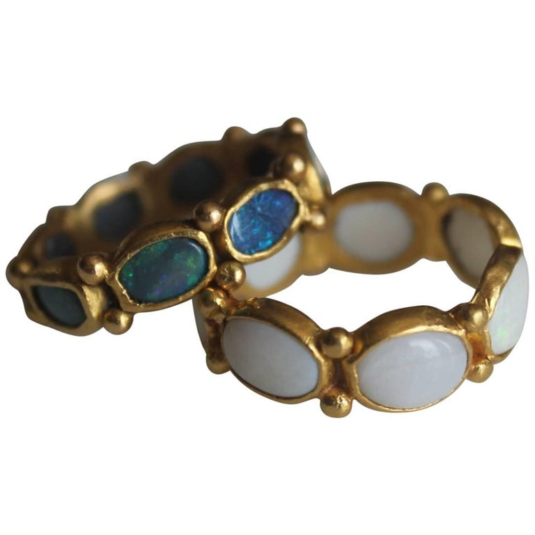 One-of-a-kind handmade 21Karat gold fashion band ring. Rich and exotic Black Opals are bezels set in solid 21k yellow gold creating a bright and interesting conversation piece. We love using opals in our designs. They are full of character with