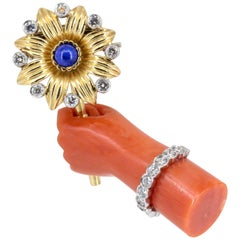 Cartier Lapis, Diamond, Coral Platinum and Gold Hand Holding Flower Brooch
