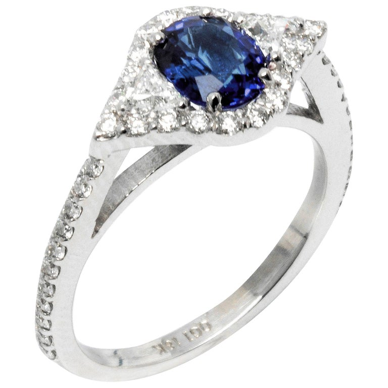 Featuring 18k white gold engagement ring with one carat sapphire and surrounded with melee diamonds.  Sapphire Weight 1.00 carat, triangle diamonds 0.25 carats and round diamond 0.70 carats. Diamond quality G VS New ring  Ring can be resized by 1/2