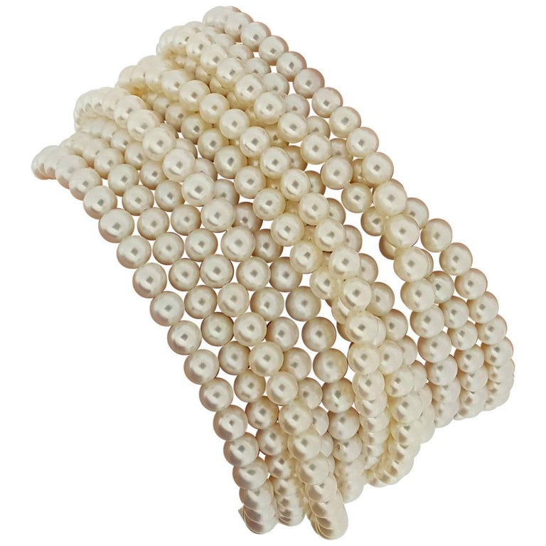 This incredible pearl bracelet designed and signed by Elizabeth Locke features 12 individual strands of pearls measuring approximately 4.5mm. The bracelet is 7.25 inches long and secured with a handmade 18kt yellow gold hammered clasp with beaded