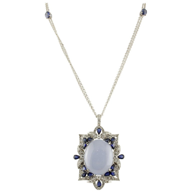Very elegant 18K white gold pendant necklace composed of amazing chalcedony in the center, all studded by white diamonds and blue sapphires around. On the two sides of the chain there are two blue sapphires. Diamonds 5.63 ct  Blue Sapphires 10.12 ct