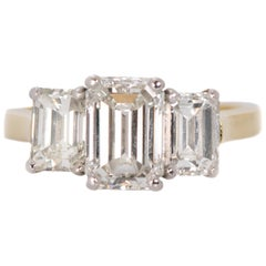 3.14 Carat Total Diamond, Platinum, 18 Karat Gold Three-Stone Emerald Cut Ring