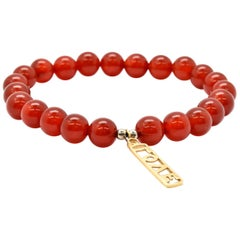 Red Jade Bead Bracelet with 14 Karat Yellow Gold Love Charm
