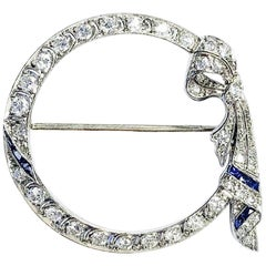 Platinum Diamond and Sapphire Art Deco Circle Ribbon Brooch