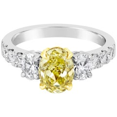 GIA Certified 1.53 Carat Oval Cut Yellow Diamond Three-Stone Engagement Ring