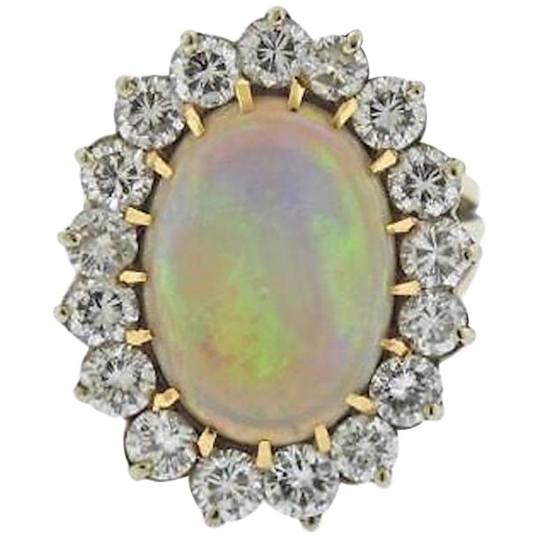This stunning ring is comprised of a gorgeous large 13 carat opal set in 14k yellow gold, surrounded by a striking large diamond halo  composed of 3.00 carats of G-H VS brilliant cut diamonds.  The ring top is 27 mmm in length and 24mm wide and the
