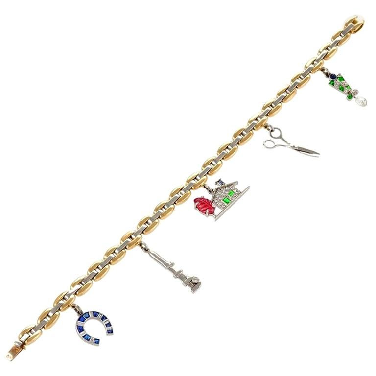 Cartier Gold, Platinum, Diamond, Sapphire, Ruby and Emerald Charm Bracelet For Sale