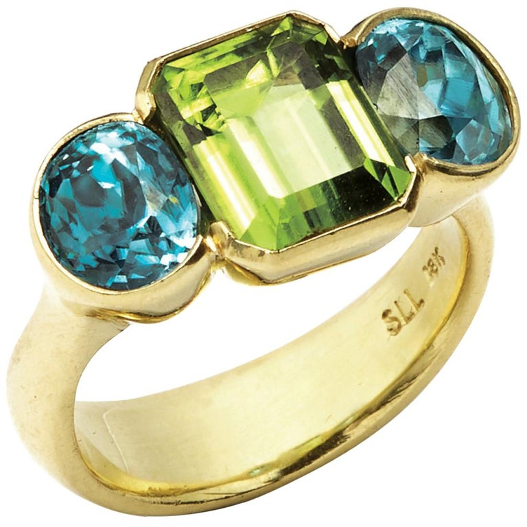 Oval Cut Zircon and Emerald Cut Peridot 18 Karat Gold Ring For Sale