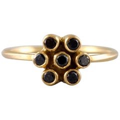 Carré ring in 18 kt. gold in the form of a flower. Adorned with 7 black diamonds