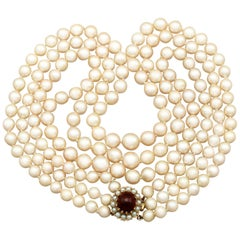 1970s Three Strand Pearl Strand with 5.91 Carat Garnet and Yellow Gold Clasp