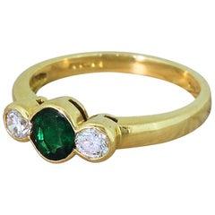 Modern Emerald and Round Brilliant Cut Diamond Trilogy Ring