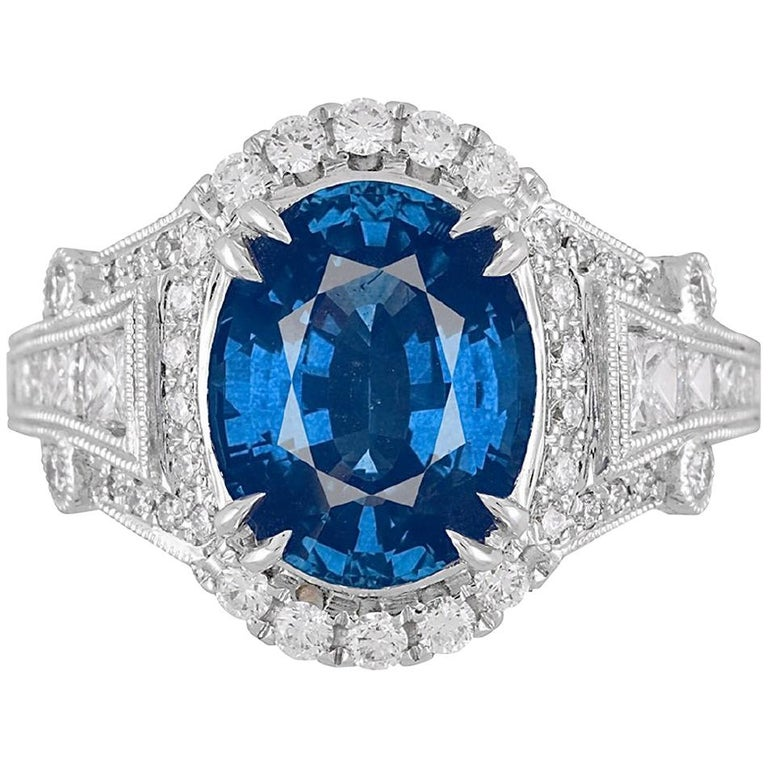(DiamondTown) With a GIA Certified 4.59 carat oval cut fine Ceylon sapphire center, and 1.01 carats white diamonds, this ring shines from every angle.  GIA Certification details (see photo): The center sapphire is Transparent, Blue, with an origin