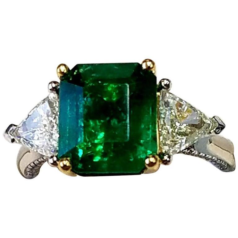 Three-Stone Platinum/ 18 Karat Yellow Gold Emerald Cut Emerald and Diamond Ring For Sale