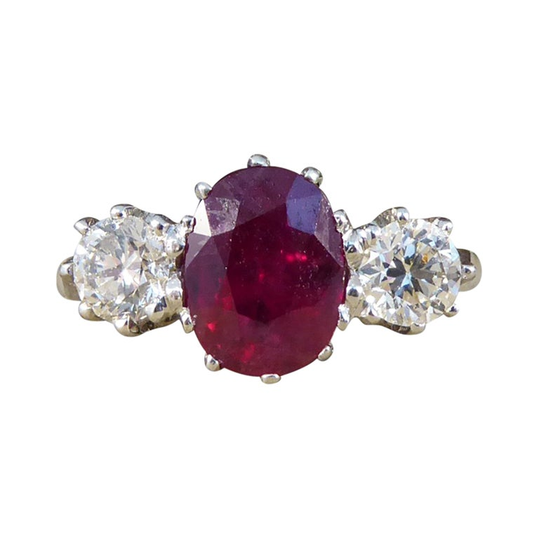 Oval Ruby and Diamond Three-Stone Engagement Ring in Platinum