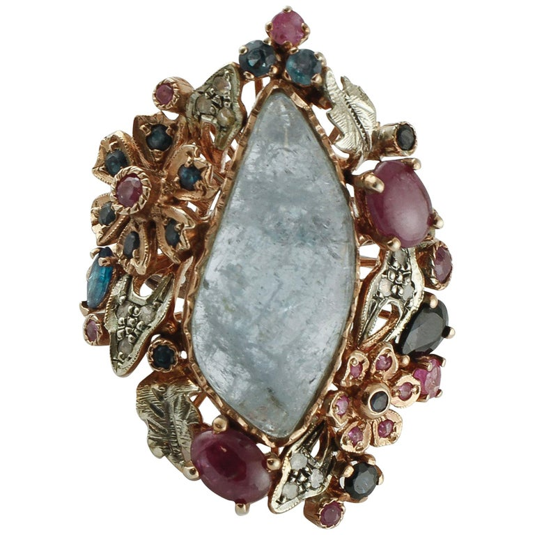 Central Aquamarine Diamonds, Rubies, Blue Sapphires 9 Karat Gold and Silver Ring For Sale