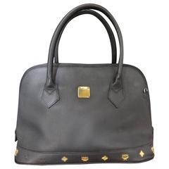 Vintage MCM black bolide style bag with gold tone charms. By Michael Cromer