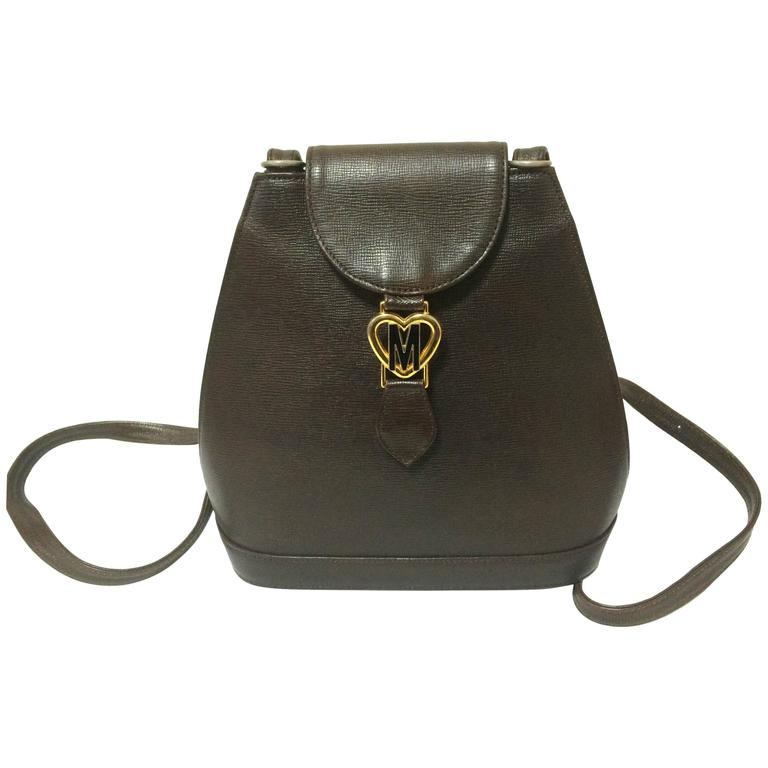 Vintage MOSCHINO dark brown leather backpack with golden and black M logo.