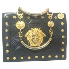 Vintage Gianni Versace black tote bag with golden medusa charms and handles.