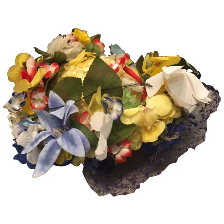 A beautiful and charming 1950s Chanda pale yellow straw hat trimmed around the small turned up brim with beautiful multi-color silk flowers and leaves.  At back is a Kelly green grosgrain bow.  A fully intact navy blue veil is attached as well as