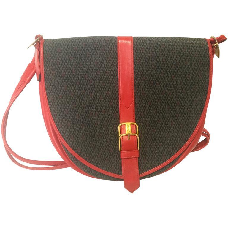 Vintage Yves Saint Laurent oval navy shoulder bag with red shoulder straps.