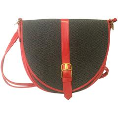 Vintage Yves Saint Laurent oval navy shoulder bag with red shoulder straps.