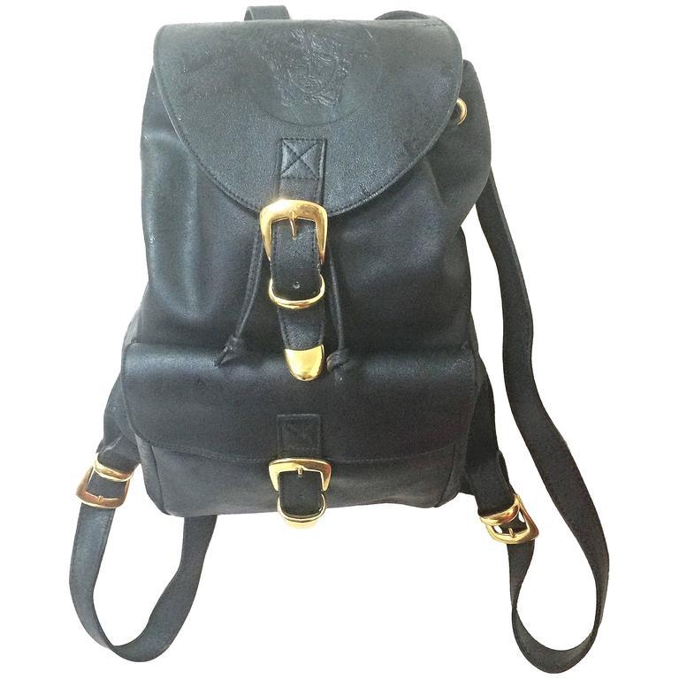 Vintage Gianni Versace black leather backpack with a big embossed medusa mark. For Sale