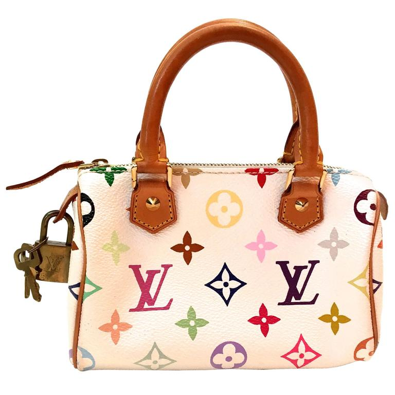 Presented here is a Mini Keepall from Louis Vuitton with a shoulder strap. This particular Mini Keepall is a discontinued style and extremely difficult to find. It is the standard tan leather with white leather background with the classic iconic