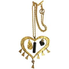 Vintage Christian Lacroix golden large heart necklace with dangling charms.