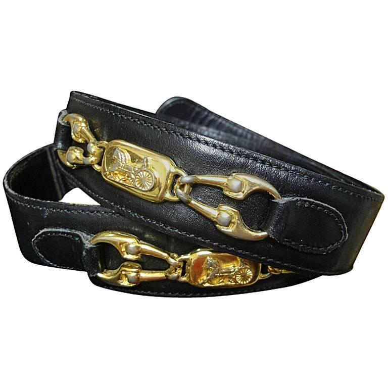 Vintage Celine black leather belt with golden carriage and horse motif. 65  1