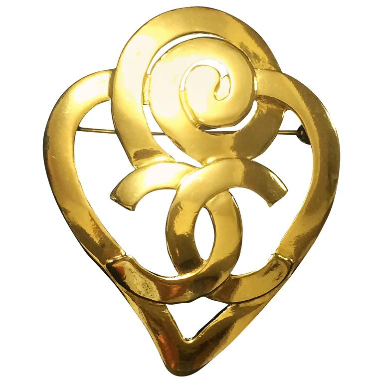 Vintage CHANEL gold tone heart and snail design brooch with CC mark at center. For Sale