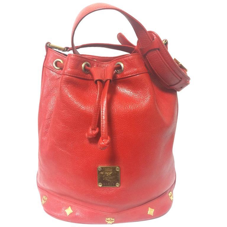 Vintage MCM genuine leather red hobo bucket shoulder bag with gold tone motifs.