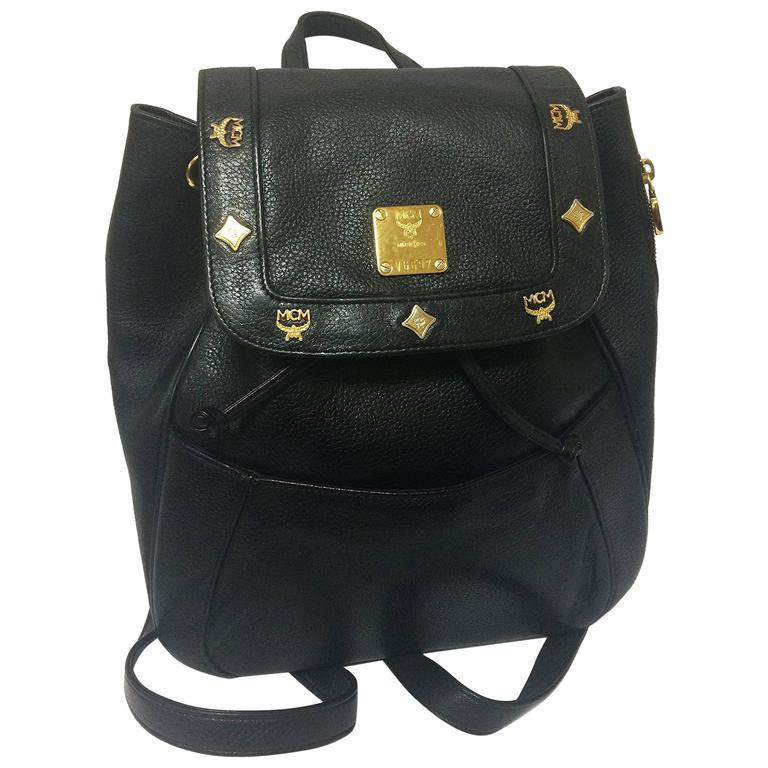 80's vintage MCM genuine leather black backpack with golden logo motifs. Unisex For Sale