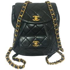 Vintage CHANEL quilted black lamb leather backpack with gold chain and CC.
