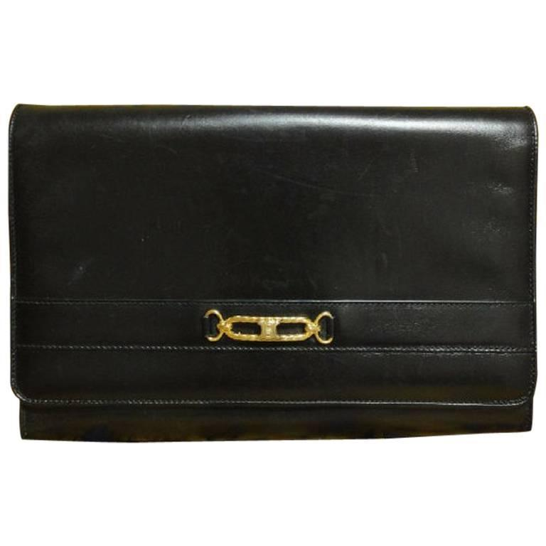 Vintage Celine black calfskin leather clutch bag with iconic golden logo motif. 1