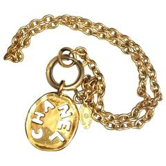 Vintage CHANEL golden chain necklace with cutout logo coin charm.