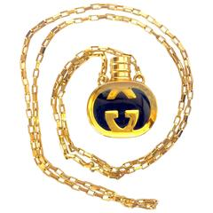 Vintage Gucci gold and navy round shape perfume bottle necklace with logo mark.