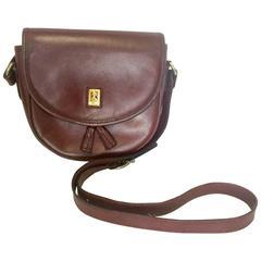 Vintage Burberry wine leather mini pouch shoulder bag with gold tone logo motif.