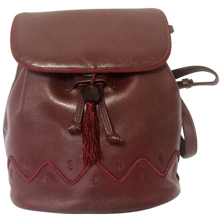 Vintage MOSCHINO dark wine leather backpack with tassel and logo embroidery. For Sale