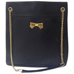 Vintage Nina Ricci black tote bag with golden chain straps with golden logo bow.