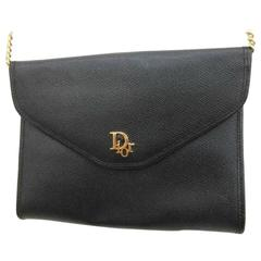 Vintage Christian Dior black leather chain clutch bag with golden logo motif.