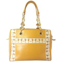 Vintage MOSCHINO yellow handbag with golden heart chains and dancing girl motif.