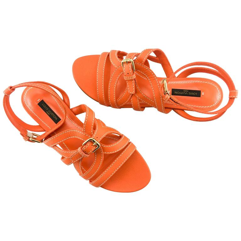 These really cool Louis Vuitton sandals are in unworn condition. Made in orange leather, these flat, strappy sandals feature one buckle on the ankle and one on the front. Really stylish, they are certain to steal the attention in the hot months of