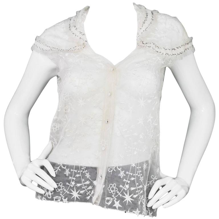 Nina Ricci White Embroidered Silk Cap Sleeve Top Features beading and fringe throughout neckline and sleeves  Made In: France Color: White Composition: 100% silk Lining: None Closure/Opening: Button up front Exterior Pockets: None Interior Pockets: