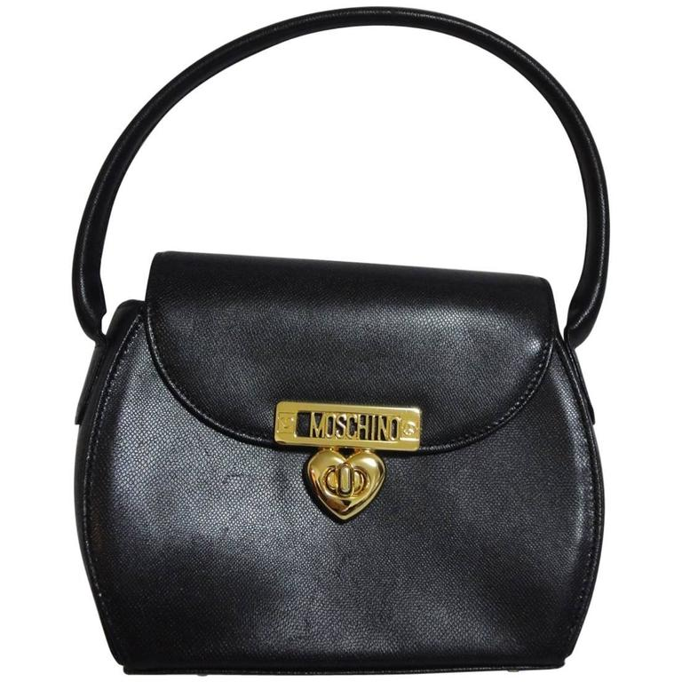Vintage MOSCHINO black leather handbag, oval shape purse with golden logo motif.
