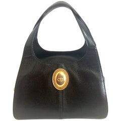 Vintage Christian Dior grained black leather handbag with oval golden CD logo.
