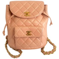 Vintage CHANEL quilted pink lamb leather backpack with golden chains and CC mark