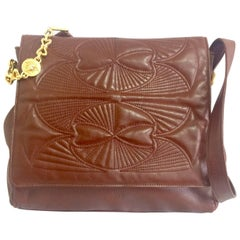Vintage Gianni Versace brown messenger shoulder bag with golden medusa motifs.