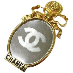 Vintage CHANEL mirror and golden bow, mademoiselle motif brooch with CC motif.